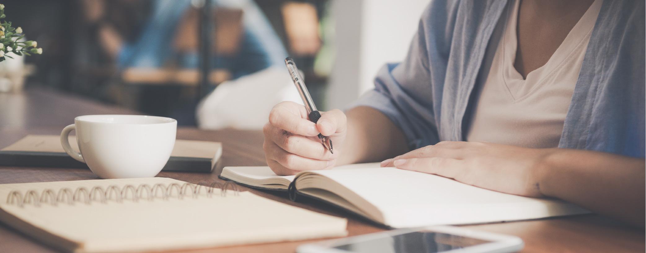 main écrivant avec un stylo dans un carnet